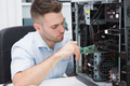 Young it professional fixing computer problem at workplace