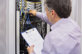 Electrician doing server maintenance with clipboard in hallway of data center