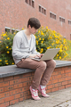 Student using laptop sitting on wall outside in college - PhotoDune Item for Sale