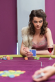 Woman sitting at the table looking at her chips in casino