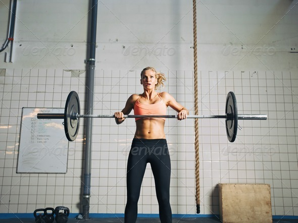 Crossfit young woman lifting heavy weights - Stock Photo - Images