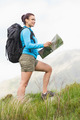 Attractive hiker with backpack walking uphill holding a map in the countryside