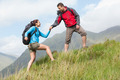Attractive hiker helping his girlfriend uphill in the countryside