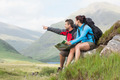 Couple taking a break after hiking uphill and holding map in the countryside
