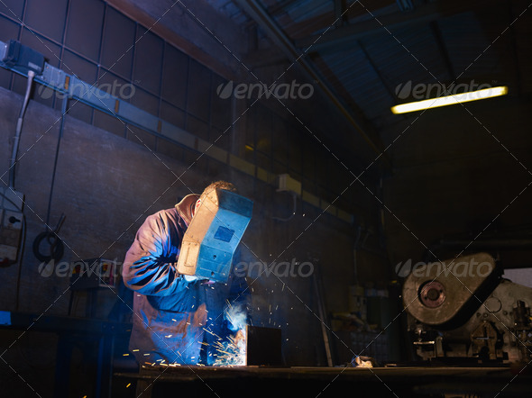 Man at work as welder in heavy industry - Stock Photo - Images
