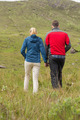 Couple holding hands and walking through the countryside