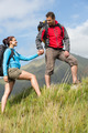 Handsome hiker helping his girlfriend uphill in the countryside