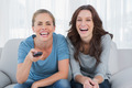 Laughing women watching television  sitting on the sofa - PhotoDune Item for Sale