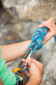 Female rock climber adjusting her harness by the rock face - PhotoDune Item for Sale