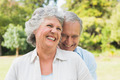 Happy mature couple laughing in the park on sunny day - PhotoDune Item for Sale