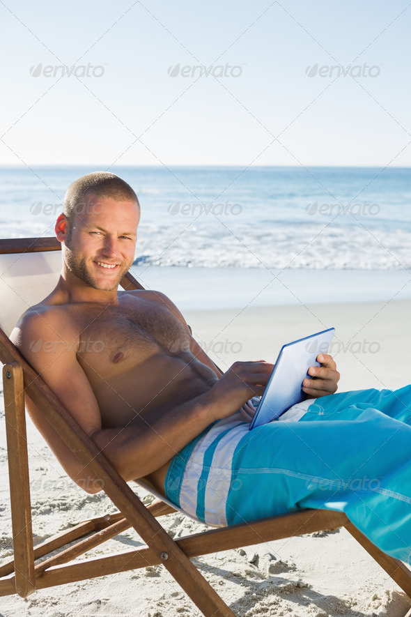 Cheerful handsome man on the beach using his tablet while sunbathing - Stock Photo - Images