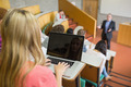 Rear view of a female using laptop with students and teacher at the college lecture hall - PhotoDune Item for Sale