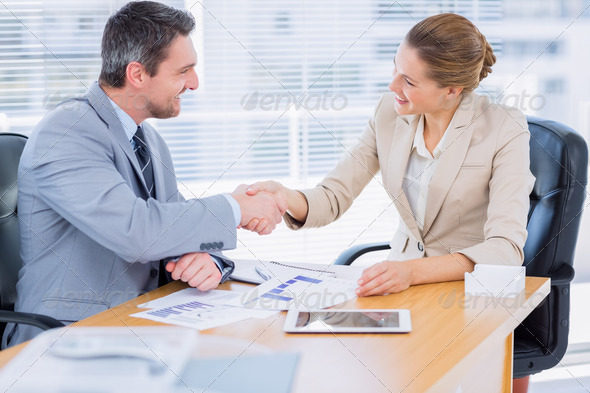 Smartly dressed young man and woman shaking hands in a business meeting at office desk - Stock Photo - Images