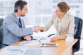 Smartly dressed young man and woman shaking hands in a business meeting at office desk - PhotoDune Item for Sale