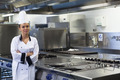 Young happy chef standing next to work surface arms crossed in professional kitchen - PhotoDune Item for Sale