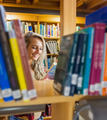 Smiling young female student reading book amid bookshelves in the college library - PhotoDune Item for Sale