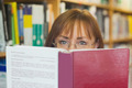 Mature female student reading a book in a library - PhotoDune Item for Sale