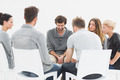 Group therapy in session sitting in a circle with therapist - PhotoDune Item for Sale