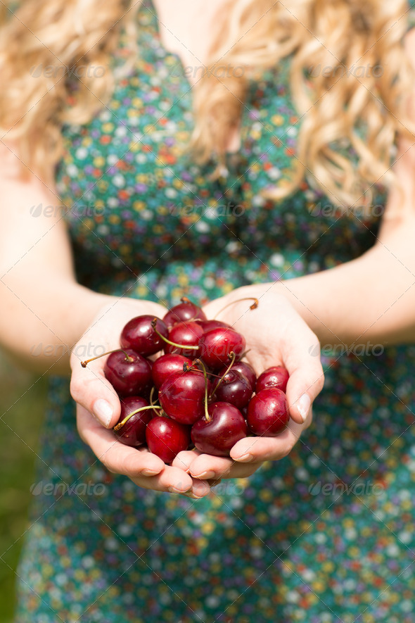 Close up of a blonde woman holding some cherries while wearing a nice dress - Stock Photo - Images