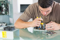 Handsome frowning computer engineer repairing hardware with pliers in bright office