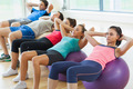 Class doing abdominal crunches on fitness balls in a row at the bright gym