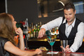 Handsome bartender serving cocktail to attractive woman in a classy bar - PhotoDune Item for Sale