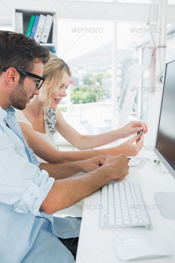 Side view of smiling casual young couple working on computer in a bright office - Stock Photo - Images