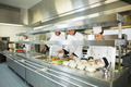 Four chefs working in a big kitchen at service time - PhotoDune Item for Sale