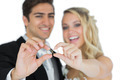 Cheerful married couple showing their wedding rings on white background