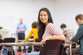 Portrait of a smiling young female student with blurred teachers and others in the classroom - PhotoDune Item for Sale