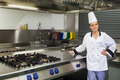 Young content chef standing next to hotplate in professional kitchen - PhotoDune Item for Sale