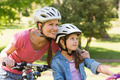 Portrait of a smiling woman with her daughter riding bicycles - PhotoDune Item for Sale