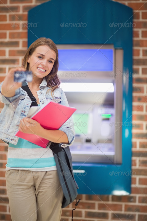 Happy student standing showing her card to camera at the atm in college - Stock Photo - Images