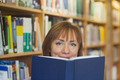 Peaceful mature woman holding a book in a library looking at camera - PhotoDune Item for Sale