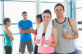 Portrait of a fit couple with friends standing in background in bright exercise room - PhotoDune Item for Sale
