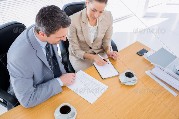 Smartly dressed young man and woman in a business meeting at office desk - Stock Photo - Images