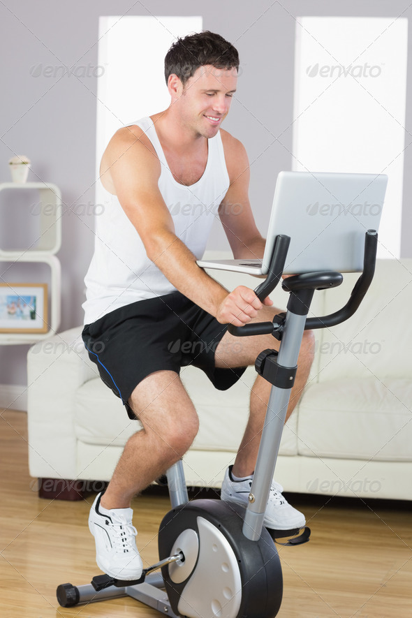 Happy sporty man exercising on bike and using laptop in bright living room - Stock Photo - Images