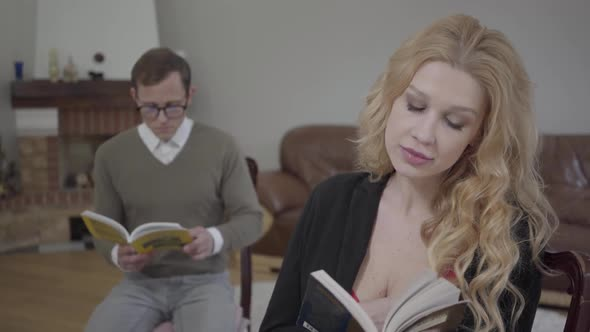 Beautiful Blond Woman Reading the Book in the Foreground While Modestly Dressed Man Studying