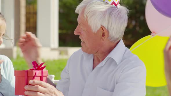 Happy Grandfather Receiving Birthday Gift from Family on Outdoor Celebration