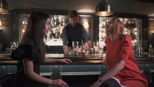 Young Girls Chatting and Laughing at the Bar on the Background of the Smiling Bartender Making