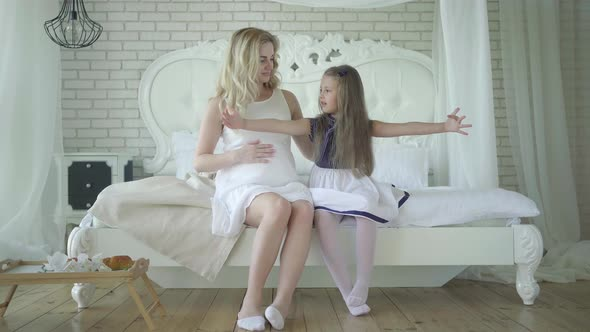 Portrait Of Pretty Little Girl Talking With Pregnant Mother In Bedroom Wide Shot Happy Caucasian By Photo Oles