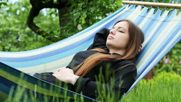 Beautiful Young Woman Sleeping on a Hammock in the Garden, Resting and Dozing