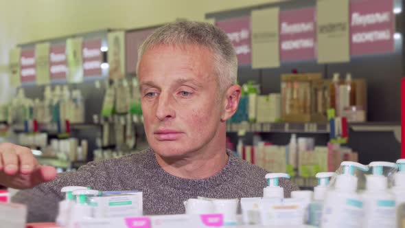Mature Man Shopping at the Drugstore, Examining Products on a Shelf