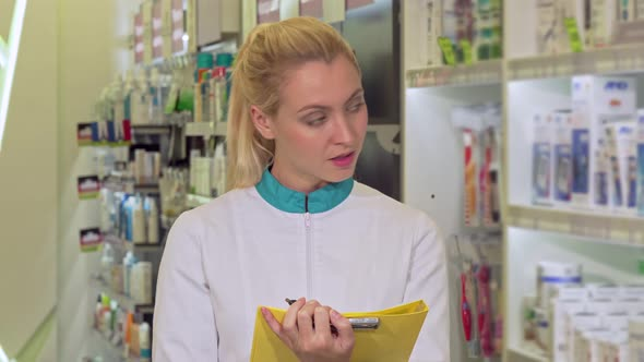 Cheerful Female Pharmacist Filling Papers, Working at the Drugstore