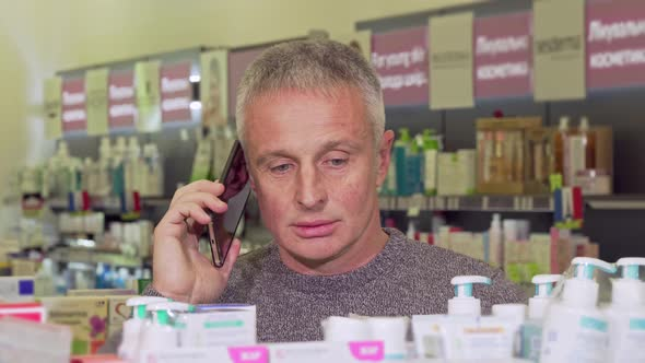 Senior Man Talking on the Phone, While Shopping at the Pharmacy