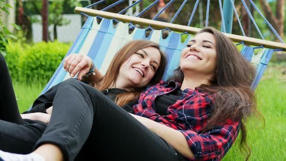 Lesbian Couple Lie in Hammock in Garden