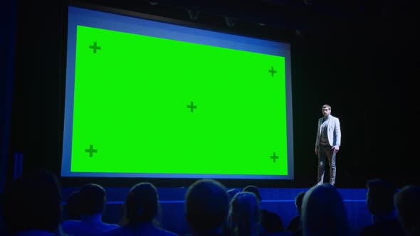 Keynote Speaker Announces New Product To The Audience Behind Him Movie Theater With Green Screen By Gorodenkoffs
