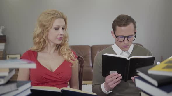 Young Modestly Dressed Man in Glasses and Curly Blond Woman Reading the Book Sitting on the Sofa