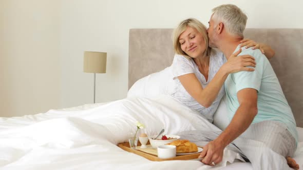 . Romantic husband bringing his happy wife breakfast in bed
