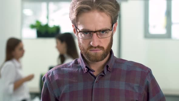 Portrait of a Bearded Guy with Glasses in a Daily Plaid Shirt Standing in the Office Center